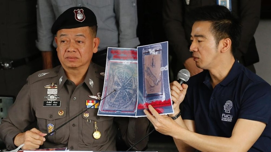 Thai police officers show pictures of a tattooed human skin during a press conference at Bangpongpang police station in Bangkok,Thailand,  Monday, Nov. 17, 2014. A shipping company in Bangkok put a trio of packages bound for the United States through a routine X-ray and made a startling discovery — inside were a variety of preserved human parts, including an infant's head, a baby's foot sliced into three sections and a tiny heart.(AP Photo/Sakchai Lalit)