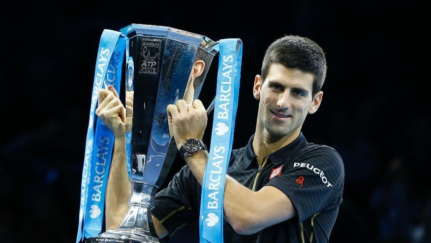 Serbia's Novak Djokovic holds up the trophy of the ATP World Tour Finals tennis after a walkover victory due an injury to Switzerland's Roger Federer in London, Sunday, Nov. 16, 2014. Federer withdrew due to an injured back. (AP Photo/Kirsty Wigglesworth)
