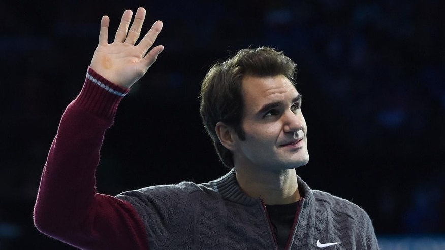 Switzerland's Roger Federer waves to the crowd after announcing his withdrawal from the final match of the ATP World Tour Finals tennis against Serbia's Novak Djokovic, due to injury in London, Sunday, Nov. 16, 2014. Federer talked to the crowd from the court to say he was sorry but he has a back injury. (AP Photo/Tim Ireland)