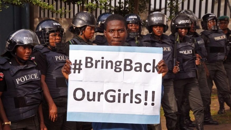 FILE-In this file photo taken on Tuesday, Oct. 14, 2014, a man poses with a sign in front of police officers in riot gear during a demonstration calling on the government to rescue the kidnapped girls of the government secondary school in Chibok, in Abuja, Nigeria. The Nigerian army has regained control of Chibok, the northeastern town where more than 200 schoolgirls were kidnapped by Islamic extremists more than six months ago, said army officials. The army wrested back control of Chibok from the Islamic militants of Boko Haram on Saturday,  Nov. 15, 2014,  Nigerian army spokesman Brigadier General Olajide Olaleye told the Associated Press. (AP Photo/Olamikan Gbemiga, File)