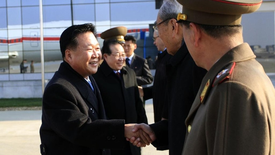 North Korean leader Kim Jong Un's special envoy Choe Ryong Hae, left, a senior member of the Presidium of the Political Bureau and secretary of the Central Committee of the Workers' Party, shakes hands with Kim Ki Nam, second right, also secretary of the Central Committee of the Workers' Party, as he and his delegation members leave the Pyongyang Airport in Pyongyang, North Korea, for Russia Monday, Nov. 17, 2014. Choe, one of Kim's close associates, left Pyongyang on Monday to discuss ways to improve trade and political ties with Russia. He is scheduled to stay in Russia until Nov. 24. (AP Photo/Jon Chol Jin)
