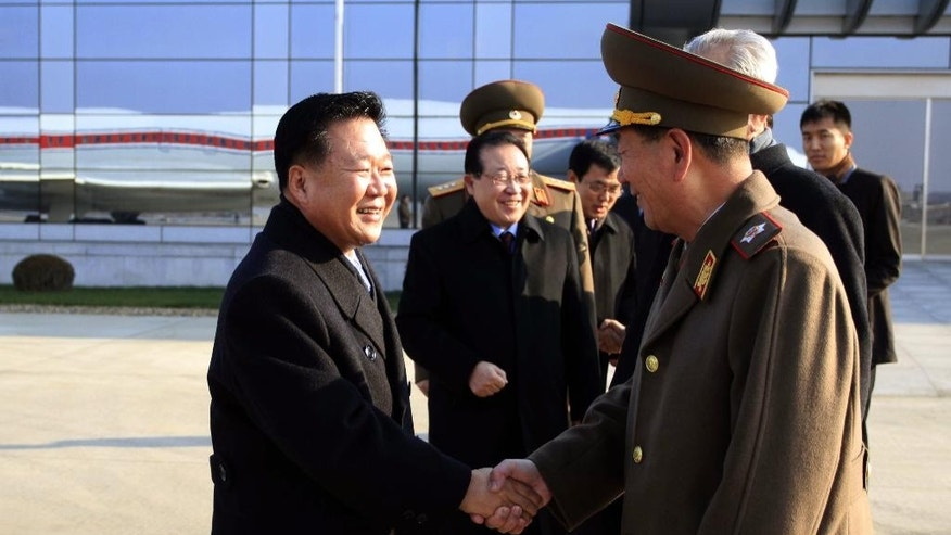 North Korean leader Kim Jong Un's special envoy Choe Ryong Hae, left, a senior member of the Presidium of the Political Bureau and secretary of the Central Committee of the Workers' Party, shakes hands with Hwang Pyong So, director of the General Political Bureau of the Korean People's Army, as he and his delegation members leave the Pyongyang Airport in Pyongyang, North Korea, for Russia Monday, Nov. 17, 2014. Choe, one of Kim's close associates, left Pyongyang on Monday to discuss ways to improve trade and political ties with Russia. He is scheduled to stay in Russia until Nov. 24. Delegation member Kim Kye Gwan, first vice-minister of Foreign Affairs, is seen second left. (AP Photo/Jon Chol Jin)