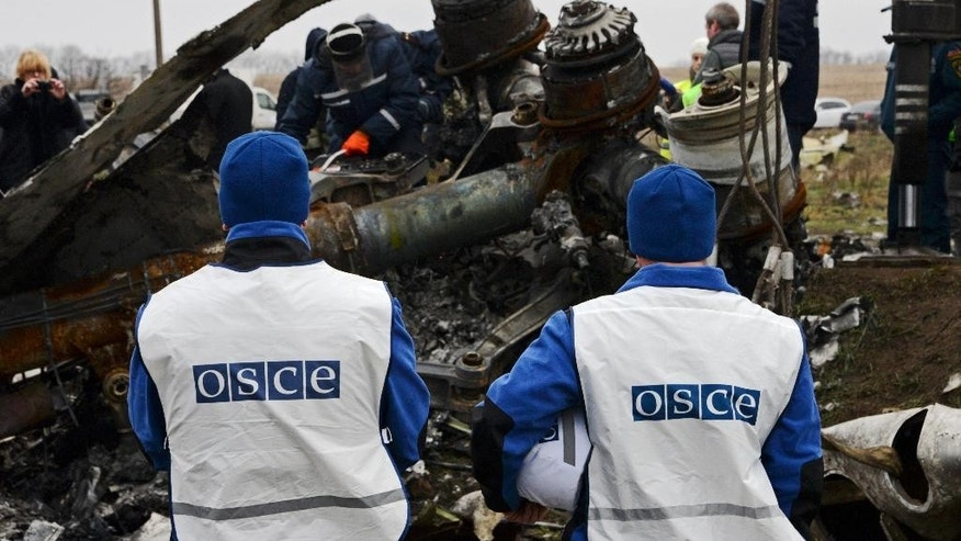 OSCE members watch as recovery workers in rebel-controlled eastern Ukraine load debris from the crash site of Malaysia Airlines Flight 17, in Hrabove, Ukraine, Sunday, Nov. 16, 2014, four months after the plane was brought down. Sunday's operation is being carried out under the supervision of Dutch investigators and officials from the Organization for Security and Cooperation in Europe. The recovered fragments will be loaded onto trains and ferried to the government-controlled eastern Ukrainian city of Kharkiv, and the investigation into the cause of the crash is being conducted there and in the Netherlands. (AP Photo/Mstyslav Chernov)