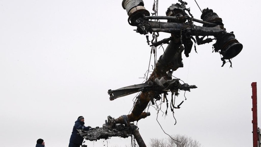 Recovery workers in rebel-controlled eastern Ukraine load debris from the crash site of Malaysia Airlines Flight 17, in Hrabove, Ukraine, Sunday, Nov. 16, 2014, four months after the plane was brought down. Sunday's operation is being carried out under the supervision of Dutch investigators and officials from the Organization for Security and Cooperation in Europe. The recovered fragments will be loaded onto trains and ferried to the government-controlled eastern Ukrainian city of Kharkiv, and the investigation into the cause of the crash is being conducted there and in the Netherlands. (AP Photo/Mstyslav Chernov)