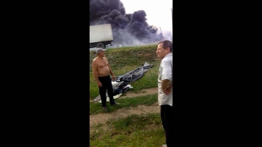 In this image made from amateur video taken on July 17, 2014 and obtained by The Associated Press, men stand near the burning wreckage of Malaysia Airlines Flight 17 near the village of Hrabove, eastern Ukraine. Four months after Malaysia Airlines Flight 17 was shot down over rebel-held eastern Ukraine, the Associated Press has obtained video material that shows how close the burning passenger jet came to hitting village homes and suggests that residents first assumed it was a Ukrainian military plane that had been struck. (AP Photo)