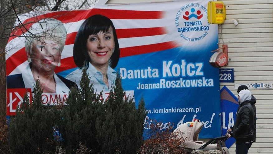 Election posters for local elections are fixed in a street close to a polling station in Lomianki near Warsaw, Poland, Sunday, Nov. 16, 2014. The voting is considered a test for the main parties ahead of the parliamentary elections next year. Some 30 million voters are eligible to choose nearly 47,000 councilors and 2,500 local administration leaders on Sunday, but observers are concerned about the possibility of a low turnout. Opinion polls gave a narrow lead to the governing pro-business Civic Platform party, over the nationalist opposition Law and Justice. (AP Photo/Czarek Sokolowski)