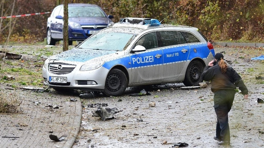 A police woman passes a destroyed police car near Homberg  Germany, Sunday Nov. 16, 2014. German police say a man injured several  people and killed himself in front of his family home by using explosives to blow himself up. Police spokesman Thomas Rodemer said the 49-year-old, whose identity was not revealed in line with German privacy law, left his home in Homberg  on Sunday after a family fight, drove away with his car and blew himself up in the car upon his return home.  Several people including family members, neighbors and two police officers who had been called to settle the family argument were slightly injured by the debris from the explosion. Neighboring homes were also damaged.   (AP Photo/dpa,Boris Roessler)