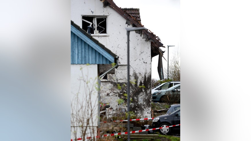 Cars stand next to a destroyed house in Homberg , Germany, Sunday Nov. 16, 2014.  German police say a man injured several  people and killed himself in front of his family home by using explosives to blow himself up. Police spokesman Thomas Rodemer said the 49-year-old, whose identity was not revealed in line with German privacy law, left his home in Homberg  on Sunday after a family fight, drove away with his car and blew himself up in the car upon his return home.  Several people including family members, neighbors and two police officers who had been called to settle the family argument were slightly injured by the debris from the explosion. Neighboring homes were also damaged.  (AP Photo/dpa,Boris Roessler)
