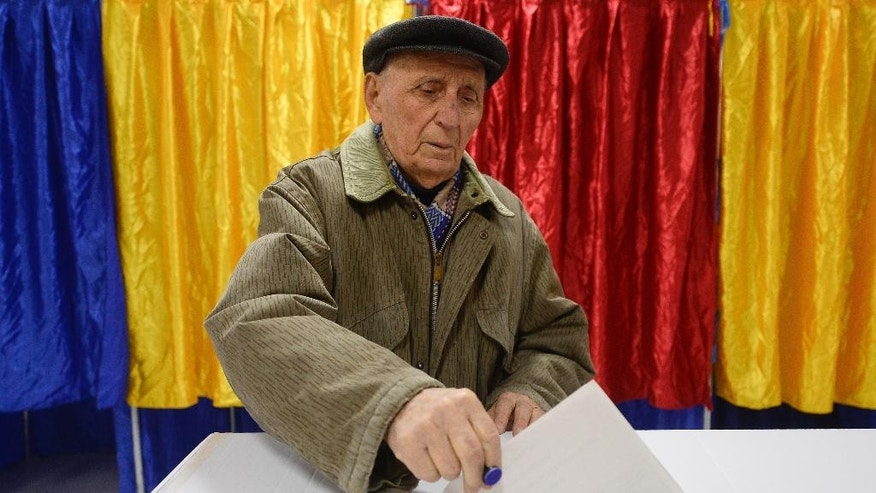 An elderly man casts his ballot in Bucharest, Romania, Sunday, Nov. 16, 2014. Romanians were voting Sunday in a presidential runoff between the prime minister who promises stability and a city mayor who says he will fight corruption. (AP Photo/Octav Ganea, Mediafax) ROMANIA OUT
