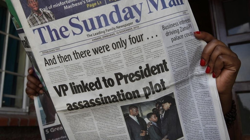 CAPTION CORRECTS THE NAME - A copy of The Sunday Mail newspaper is held in Harare, Sunday, Nov. 16, 2014, showing the story of the Vice President being linked to a presidential assassination plot. Zimbabwe's vice president Joice Mujuru, once seen as a possible successor to president Robert Mugabe, has been linked to an alleged plot to assassinate the 90-year-old leader, the state-run newspaper reported. (AP Photo/Tsvangirayi Mukwazhi)