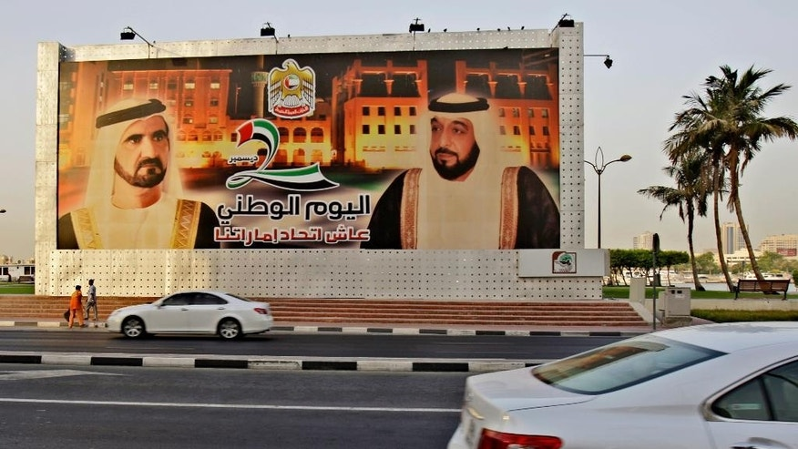 """FILE-- In this July 30, 2009 file photo, cars pass by a billboard showing Sheik Mohammed bin Rashid Al-Maktoum, United Arab Emirates Prime Minister and ruler of Dubai, left, and UAE President Sheik Khalifa bin Zayed Al-Nahyan with Arabic writing that reads, 'Long live Emirates unity, National Day' in Dubai, UAE. The UAE has quietly mounted """"an unprecedented clampdown on dissent"""" since 2011, with more than 100 political activists jailed or prosecuted for calling for political reforms, leading human rights group Amnesty International said in a report released Monday. The UAE is ruled by families, like much of the energy-rich Gulf. (AP Photo/Kamran Jebreili, File)"""