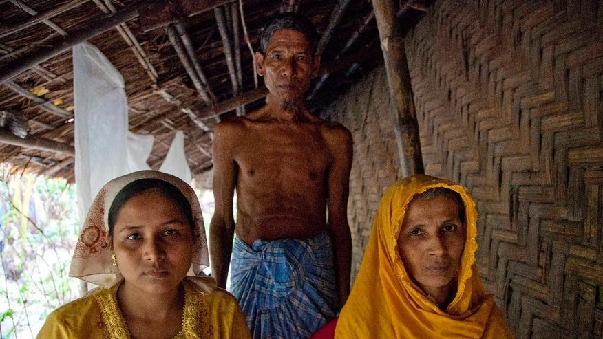 In this June 19 2014 photo, Shabu Kuna, left and her mother Rokima khatu right and father Habi Bullah, center at their home in Myin Hlut Village, South of Maung Daw. Around 80 percent of Myanmar's Rohingya live in northern Rakhine, which sits along the coast of the Bay of Bengal. Cut off front the rest of the country by a parallel running mountain range, security forces have for decades operated in the region with almost complete impunity. The depth of hatred they feel for members of the religious minority is palpable. It's something Shabu Kuna, just 23, felt every day.(AP Photo/ Esther Htusan)