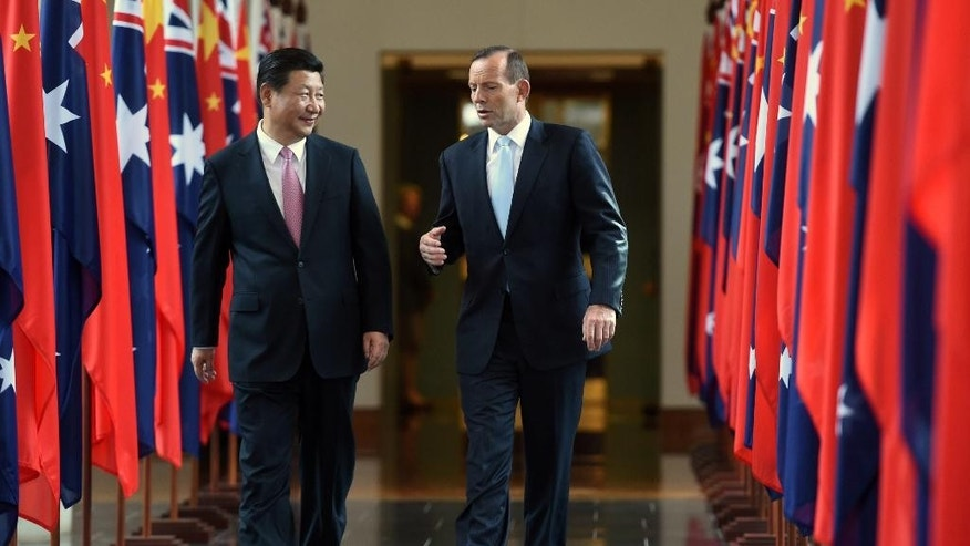Chinese President Xi Jinping, left, and Australian Prime Minister Tony Abbott walk together as they leave the House of Representatives at Parliament House in Canberra, Monday, Nov. 17, 2014. President Xi, who attended the G20 leadership summit in Brisbane,  made an address to the Australian Parliament. (AP Photo/Lukas Coch, Pool)