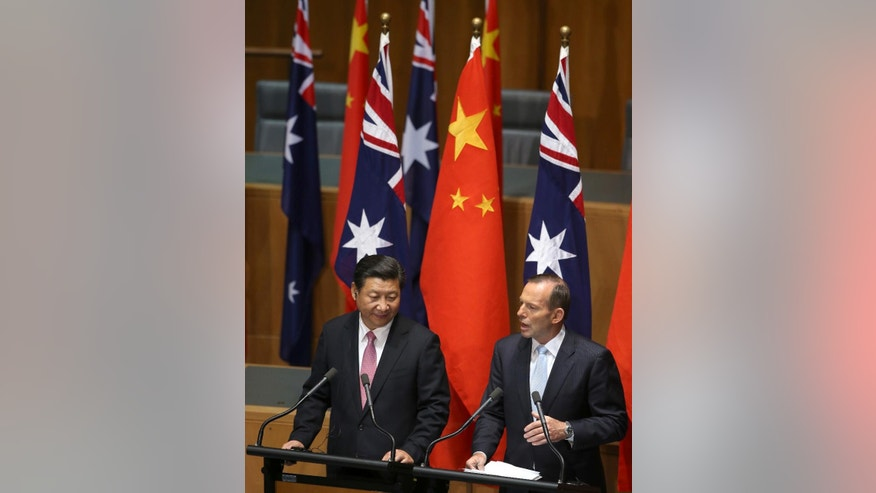 China's President Xi Jinping, left, and Australian Prime Minister Tony Abbott speak at a press conference following the signing of several memorandums of understanding to strengthen trade in Canberra, Monday, Nov. 17, 2014. Two-way flow of goods and services between the countries was valued at more than $130 billion last year. (AP Photo/Rick Rycroft)