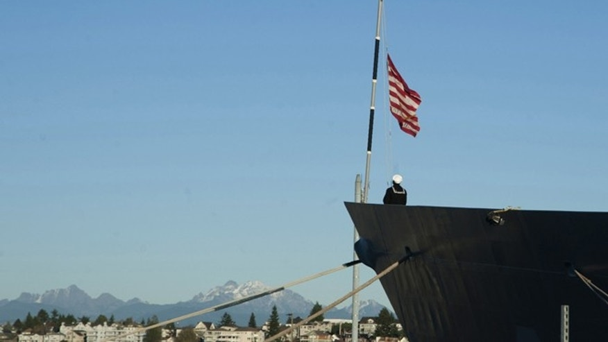 A sailor on the USS Ingraham lowers the Navy Jack on Wednesday, Nov. 12, 2014 in Everett, Wash. (AP Photo/U.S. Navy, Petty Officer 2nd Class Jeffry A. Willadsen, Released)