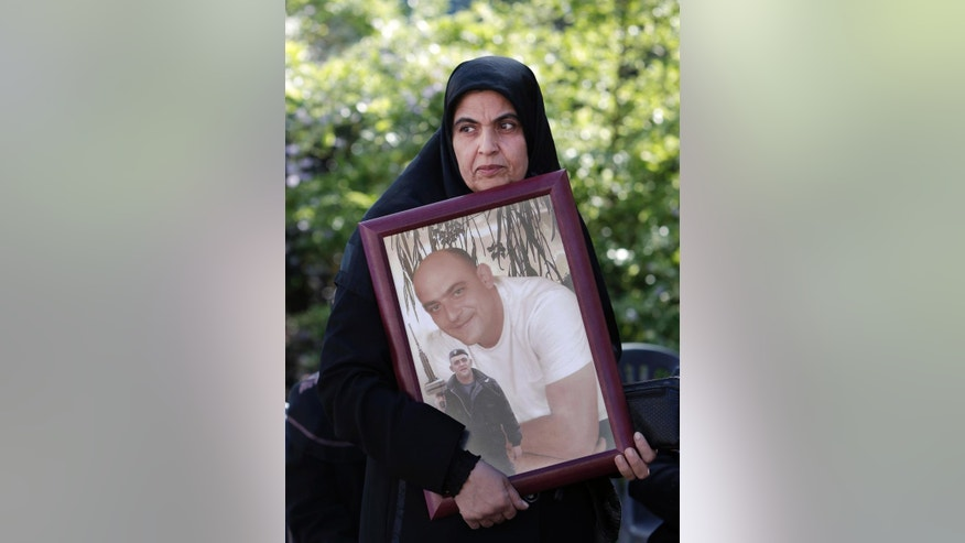 Inaam Omar, 50, aunt of one Lebanese soldier Ziad Omar who was kidnapped by Islamic militants, holds his picture during a demonstration to demand action to secure the captives' release, in front of government heaquarters in downtown Beirut, Lebanon, Monday, Nov. 17, 2014. The militants, including the al-Qaida linked Nusra Front and the extremist Islamic State group, are holding some 20 Lebanese soldiers and policemen hostages since August, when they briefly overran a Lebanese border town. (AP Photo/Bilal Hussein)