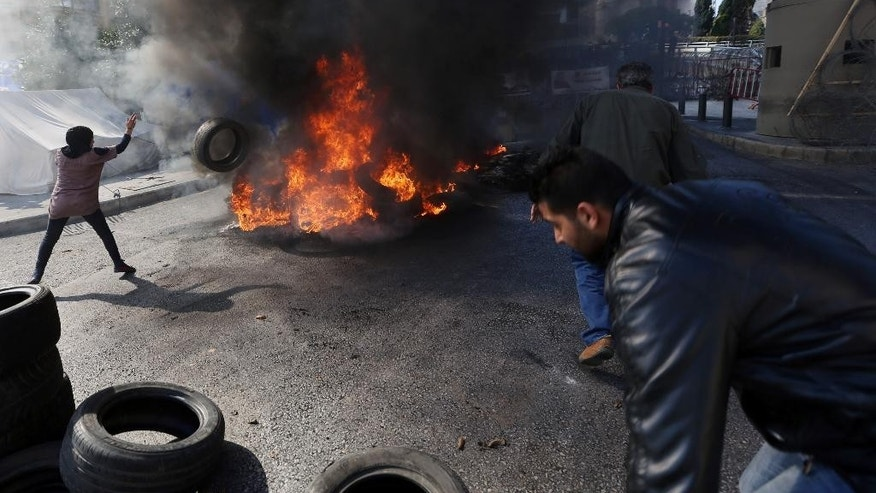 Relatives of Lebanese soldiers held hostage by Islamic militants burn tires, during a demonstration to demand action to secure the captives' release, in front of the government headquarters in downtown Beirut, Lebanon, Monday, Nov. 17, 2014. The militants, including the al-Qaida linked Nusra Front and the extremist Islamic State group, are holding some 20 Lebanese soldiers and policemen hostages since August, when they briefly overran a Lebanese border town. (AP Photo/Bilal Hussein)