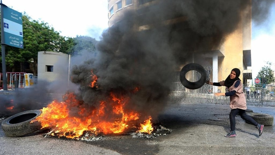 Iman Alsaid, a relative of Lebanese soldier Khalid Hassan who was kidnapped by Islamic militants, burns tires during a demonstration to demand action to secure captive soldiers' release, in front of government headquarters in downtown Beirut, Lebanon, Monday, Nov. 17, 2014. The militants, including the al-Qaida linked Nusra Front and the extremist Islamic State group, are holding some 20 Lebanese soldiers and policemen hostages since August, when they briefly overran a Lebanese border town. (AP Photo/Bilal Hussein)