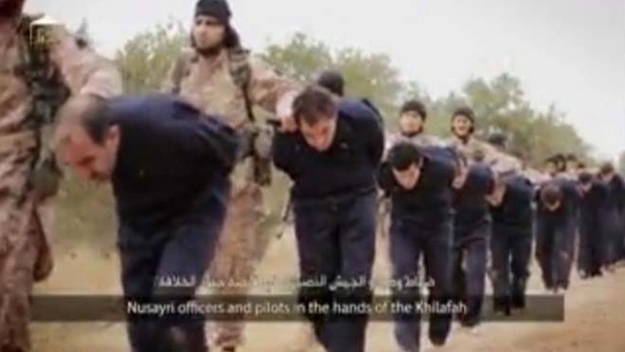 This still image taken from an undated video published on the Internet by the Islamic State group militants and made available, Sunday, Nov. 16, 2014, purports to show extremists marching Syrian soldiers before beheading them.