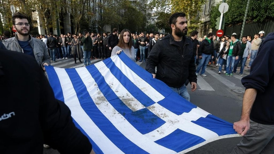 University students hold a blood-stained Greek flag from the deadly 1973 student uprising, in Athens on Monday, Nov. 17, 2014. About 7,000 police planned a major deployment that started Saturday, leading up to Monday's anniversary of a 1973 bloody student uprising against a military dictatorship. Several labor demonstrations are planned for Monday along with an annual march to the U.S. embassy in Athens. (AP Photo/Thanassis Stavrakis)