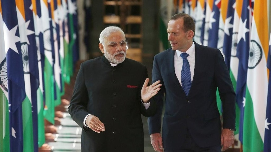 India's Prime Minster Narendra Modi, left, and Australian Prime Minister Tony Abbott walk together as they leave the House of Representatives at Parliament House in Canberra, Tuesday, Nov. 18, 2014. Modi is having bilateral talks with the Australian leader following the G-20 summit. (AP Photo/Rick Rycroft, Pool)