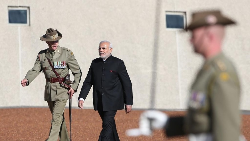 India's Prime Minster Narendra Modi, center, inspects a honor guard during a ceremonial welcome in Canberra, Tuesday, Nov. 18, 2014. Modi is having bilateral talks with Australia following on from the G20 summit. (AP Photo/Rick Rycroft)