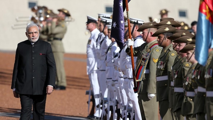 India's Prime Minster Narendra Modi, left, inspects a honor guard during a ceremonial welcome in Canberra, Tuesday, Nov. 18, 2014. Modi is having bilateral talks with Australia following on from the G20 summit. (AP Photo/Rick Rycroft)