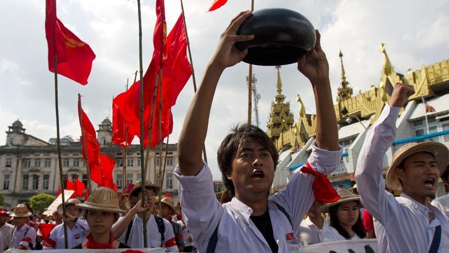 In this Nov. 17, 2014 photo,  a university student holds an alms bowl rotated upside down, a sign of protest to government, as they march to protest against National Education Law in downtown Yangon, Myanmar. Students in Myanmar are threatening to hold nationwide protests unless the government amends an education law that they say restricts their academic freedom and prohibits them from engaging in political activities. After rallying in the streets of Yangon for four consecutive days Monday - and defying the threat of arrest - they gave the government 60 days to meet their demands.(AP Photo/Khin Maung Win)