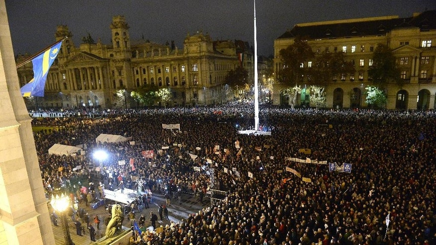 Demonstrators gather on the Kossuth Square in front of the Hungarian Parliament building during an anti-goverment demonstration called Day of Public Outcry in Budapest, Hungary, Monday Nov. 17, 2014. (AP Photo/MTI, Lajos Soos)