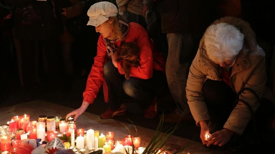 Women place candles to commemorate the 25th anniversary of the so-called Velvet Revolution in Prague, Czech Republic, Monday, Nov. 17, 2014. (AP Photo/Petr David Josek)
