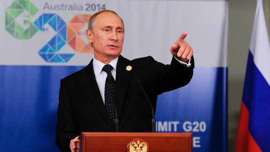 In this photo taken on Saturday, Nov. 15, 2014, Russian President Vladimir Putin speaks to the media before departing from the G-20 summit in Brisbane, Australia. Russian President Vladimir Putin made an early exit on Sunday from a two-day summit of world leaders where he was roundly criticized over Russia's escalating aggression in Ukraine, but brushed off suggestions that he had felt pressured. (AP Photo/RIA-Novosti, Mikhail Klimentyev, Presidential Press Service)