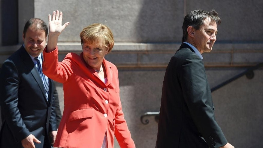 German Chancellor Angela Merkel, center, waves to well-wishers as she arrives at the ANZAC Memorial in Hyde Park in Sydney on Monday, Nov. 17, 2014. Chancellor Merkel is in Sydney following her attendance at the G20 summit in Brisbane.(AP Photo/Paul Miller, Pool)