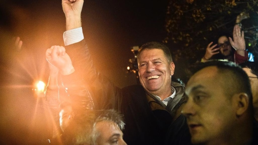 Klaus Iohannis, leader of Romania's center-right Liberals and mayor of the Transylvanian city of Sibiu, smiles waving to supporters gathered to celebrate his victory in a presidential runoff in Bucharest, Romania, early Monday, Nov. 17, 2014. Romania's Prime Minister Victor Ponta conceded defeat Sunday night in an extremely close presidential runoff against an ethnic German Transylvanian mayor. Ponta had been the favorite to win, but was narrowly edged out by Klaus Iohannis. (AP Photo/Raed Krishan)