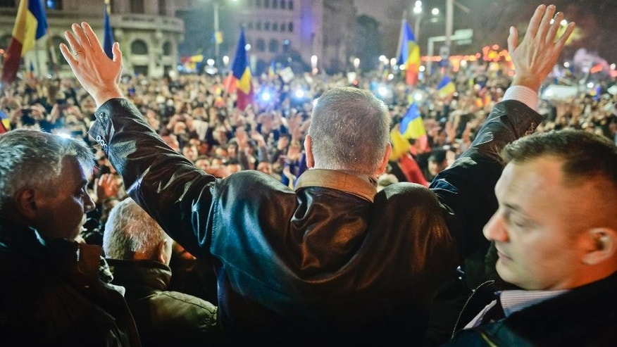 Klaus Iohannis, leader of Romania's center-right Liberals and mayor of the Transylvanian city of Sibiu, waves to supporters gathered to celebrate his victory in a presidential runoff in Bucharest, Romania, early Monday, Nov. 17, 2014. Romania's Prime Minister Victor Ponta conceded defeat Sunday night in an extremely close presidential runoff against an ethnic German Transylvanian mayor. Ponta had been the favorite to win, but was narrowly edged out by Klaus Iohannis. (AP Photo/Raed Krishan)