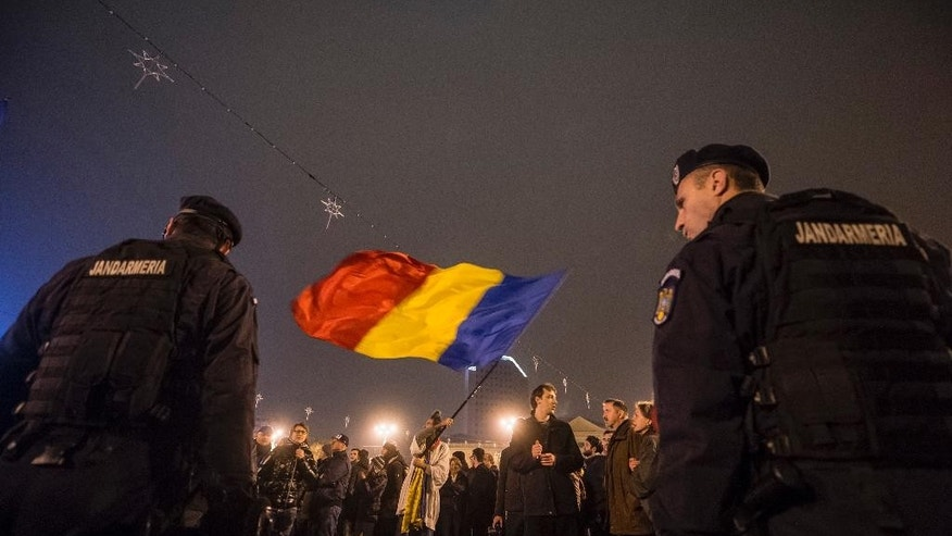 In this Sunday, Nov. 16, 2014 photo, a man waves the Romanian flag in front of a row of gendarmes, celebrating Klaus Iohannis's victory in the presidential elections in Bucharest, Romania, Sunday, Nov. 16, 2014. Thousands of people gathered in Bucharest to celebrate after Romania's prime minister conceded defeat Sunday night in an extremely close presidential runoff against the ethnic German Transylvanian mayor. (AP Photo/Andreea Alexandru, Mediafax) ROMANIA OUT