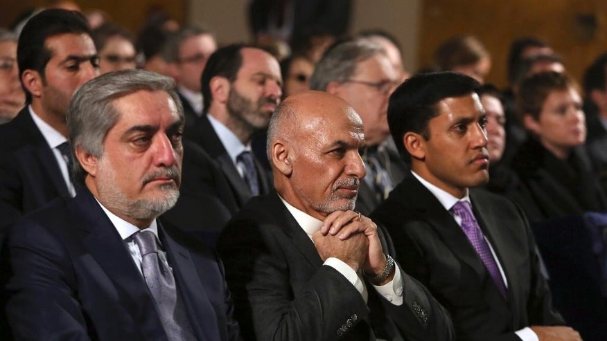 FILE - In this Saturday, Nov. 8, 2014 file photo, Afghan President Ashraf Ghani, center, sits next to chief executive Abdullah Abdullah, left, while attending an event for the Afghan Women's Empowerment Grants Program in Kabul, Afghanistan. Ghani and former rival Abdullah are restructuring the country's long-troubled government to focus on security, the economy and social policy ahead of a vital donor conference in December. Ghani became president in September, promising to reverse the legacy of corruption and nepotism of his predecessor Hamid Karzai's 13 years in office. (AP Photo/Rahmat Gul, File)