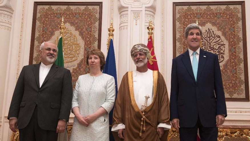 In this Sunday, Nov. 9, 2014, file photo, posing for a photo are, from left, Iranian Foreign Minister Javad Zarif,  European Union adviser Catherine Ashton, Omani Minister Responsible for Foreign Affairs Yussef bin Alawi and US Secretary of State John Kerry,  in Muscat. Iran and six world powers are closer than ever to a deal that would crimp Tehran's ability to make nuclear arms - a status that would lead to a progressive end to sanctions on the Islamic Republic and ease tensions that could boil over into a new Middle East war. The bad news? Substantial differences remain. (AP PHOTO/NICHOLAS KAMM, POOL)