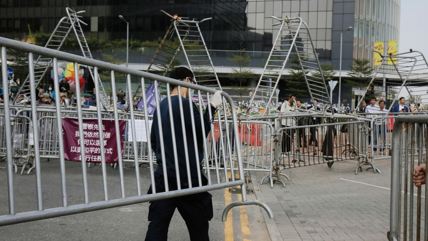 Nov. 18, 2014: A pro-democracy protester removes barricades from an occupied area outside government headquarters in Hong Kong's Admiralty district