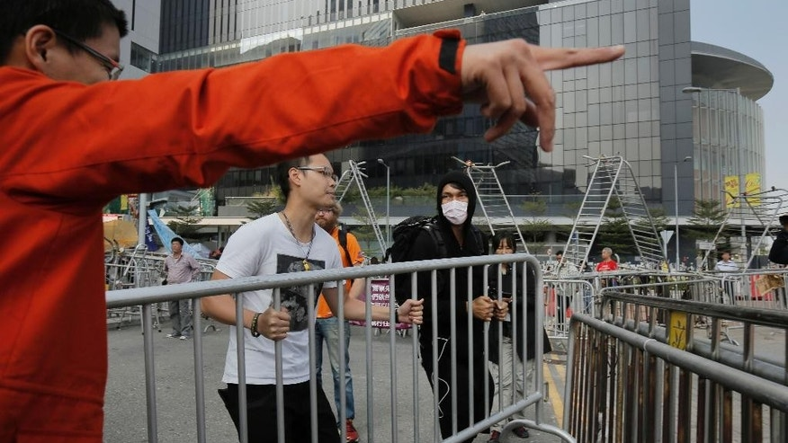 Pro-democracy protesters remove barricades from an occupied area outside government headquarters in Hong Kong's Admiralty district Tuesday, Nov. 18, 2014. Workers in Hong Kong on Tuesday started clearing away barricades at one site of the student protest that has rocked the city for the last two months. The removal comes after a Hong Kong court granted a restraining order against the protesters last week requiring them to clear the area in front of a tower in the central part of Hong Kong as well a separate order against a second protest site Mong Kok brought by taxi and minibus operators. (AP Photo/Vincent Yu)