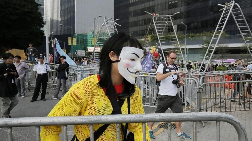 A pro-democracy protester removes barricades from an occupied area outside government headquarters in Hong Kong's Admiralty district Tuesday, Nov. 18, 2014. Workers in Hong Kong on Tuesday started clearing away barricades at one site of the student protest that has rocked the city for the last two months. The removal comes after a Hong Kong court granted a restraining order against the protesters last week requiring them to clear the area in front of a tower in the central part of Hong Kong as well a separate order against a second protest site Mong Kok brought by taxi and minibus operators. (AP Photo/Vincent Yu)