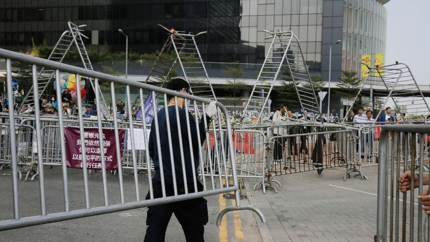 A pro-democracy protester removes barricades from an occupied area outside government headquarters in Hong Kong's Admiralty district Tuesday, Nov. 18, 2014. The removal comes after a Hong Kong court granted a restraining order against the protesters last week requiring them to clear the area in front of a tower in the central part of Hong Kong as well a separate order against a second protest site Mong Kok brought by taxi and minibus operators. (AP Photo/Vincent Yu)
