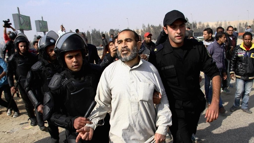 FILE - In this Wednesday, Jan. 8, 2014 file photo, Egyptian riot police officers arrest a man following clashes between supporters of Egypt's ousted President Mohammed Morsi and riot police in Cairo, Egypt. The Arabic Network for Human Rights Information, an Egyptian rights group said Tuesday, Nov. 18, 2014, that the government has repeatedly violated the country's new constitution, calling it a crime that must be addressed immediately. Authorities have rounded up thousands in a security crackdown following the overthrow of Islamist President Mohammed Morsi last year. (AP Photo/Ahmed Gomaa, File)