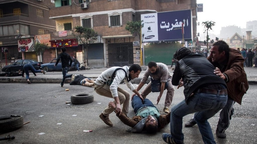 FILE - In this Saturday, Jan. 25, 2014 file photo, a mortally wounded supporter of Egypt's ousted Islamist president is evacuated as another wounded protester lies in the street during clashes with security forces in the Mohandiseen district of Cairo, Egypt. The Arabic Network for Human Rights Information, an Egyptian rights group said Tuesday, Nov. 18, 2014, that the government has repeatedly violated the country's new constitution, calling it a crime that must be addressed immediately. Authorities have rounded up thousands in a security crackdown following the overthrow of Islamist President Mohammed Morsi last year.  (AP Photo/Eman Helal, File)