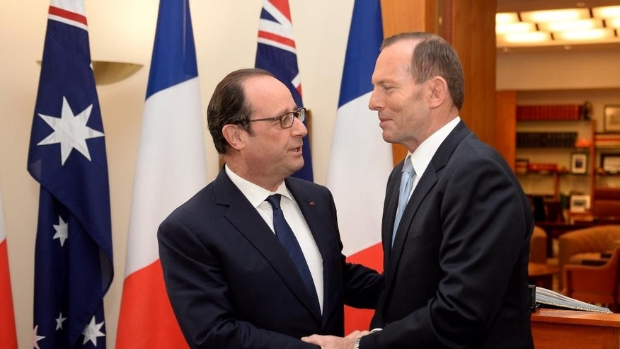 French President Francois Hollande, left, meets Australian Prime Minister Tony Abbott at Parliament House in Canberra, Australia Wednesday, Nov. 19, 2014. It is the first state visit by a French president to Australia. (AP Photo/Alan Porritt, Pool)