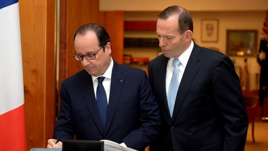 French President Francois Hollande, left, signs a guest book as Australian Prime Minister Tony Abbott watches at Parliament House in Canberra, Australia Wednesday, Nov. 19, 2014. It is the first state visit by a French president to Australia. (AP Photo/Alan Porritt, Pool)