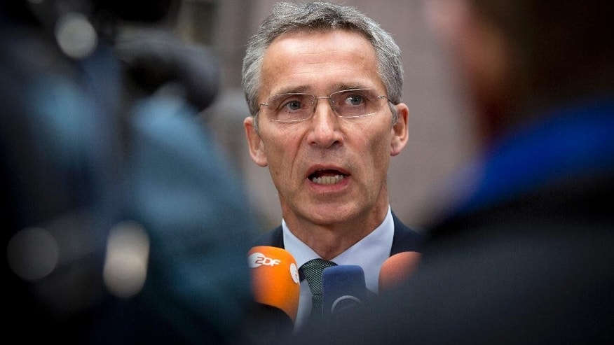 NATO Secretary General Jens Stoltenberg speaks with the media as he arrives for a meeting with EU defense ministers at the EU Council building in Brussels on Tuesday, Nov. 18, 2014. (AP Photo/Virginia Mayo)