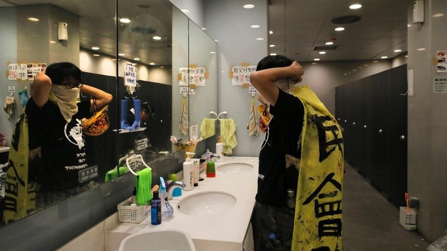 A protester adjusts his towel to cover his face in a toilet after protesters tried to break into the Legislative Council in Hong Kong early Wednesday, Nov. 19, 2014. Protesters clashed with police early Wednesday after they tried to break into Hong Kong's Legislative Council building.  (AP Photo/Vincent Yu)
