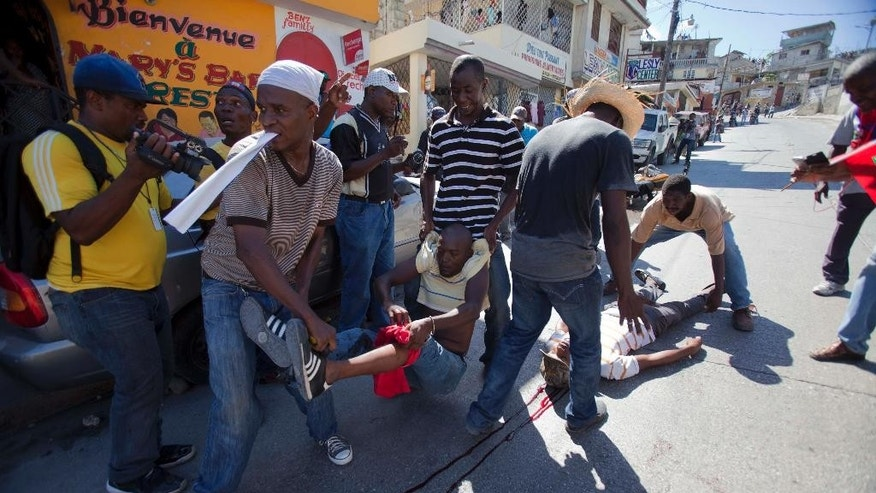 Protesters aid a man who was shot in the leg, left, and another who was shot in the neck, lying on the ground, after clashes broke out at an anti-government protest in Port-au-Prince, Haiti, Tuesday, Nov. 18, 2014. The march began peacefully when a crowd grew to a few thousand people in slums that are opposition strongholds. But as demonstrators walked through Delmas 32, the critics of President Michel Martelly's administration and pro-government residents began throwing rocks at each other. (Photo/Dieu Nalio Chery)