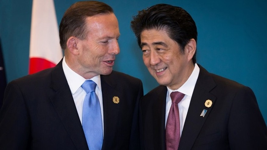 November 16, 2014: Australian Prime Minister Tony Abbott, left, and Japanese Prime Minister Shinzo Abe, right, talk as they wait for U.S. President Barack Obama to arrive to start their meeting at the G-20 Summit in Brisbane, Australia. (AP Photo/Ian Waldie,Pool)