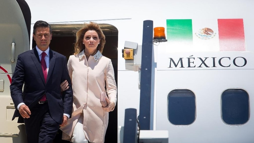 FILE - In this Nov. 14, 2014, file photo, released by G20 Australia, President of Mexico Enrique Pena Nieto and first lady Angelica Rivera Hurtado arrive at Brisbane Airport ahead of the G-20 summit in Brisbane, Australia. President Pena Nieto said Tuesday Nov. 18, that the first lady will clarify questions about a multimillion-dollar home that has raised concerns about possible conflict of interest, even as his government grapples with protests over the disappearance of 43 teachers college students. (AP Photo/G20 Australia, Patrick Hamilton, File)